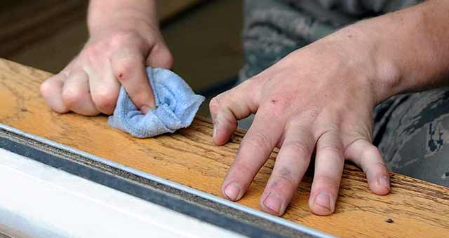 A man removing stain from wood by using a wood stain remover